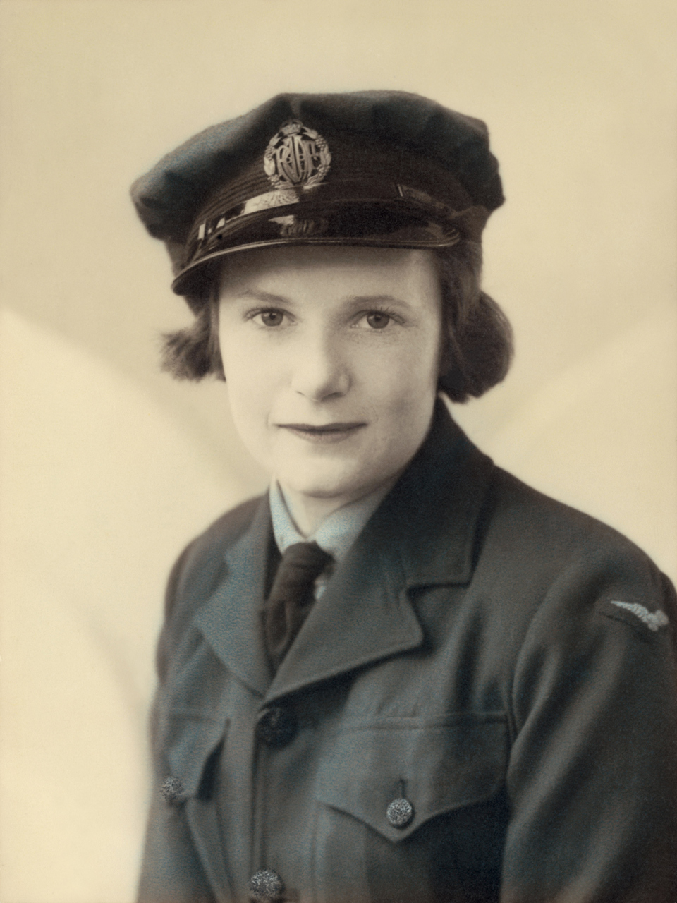 Studio portrait of 111548 Aircraftwoman Marie Isabel COOTE, taken circa 1944. The photographer is unknown. This version of the portrait has been hand-coloured. All photographs shown here are from the Mollie WILSON (nee COOTE) collection unless otherwise noted.